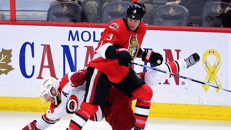 Carolina Hurricanes' Jordan Staal gets pushed to the ice by Ottawa Senators' Marc Methot during the second period of an NHL hockey game in Ottawa, Tuesday, Nov. 1, 2016. (Sean Kilpatrick/The Canadian Press via AP)