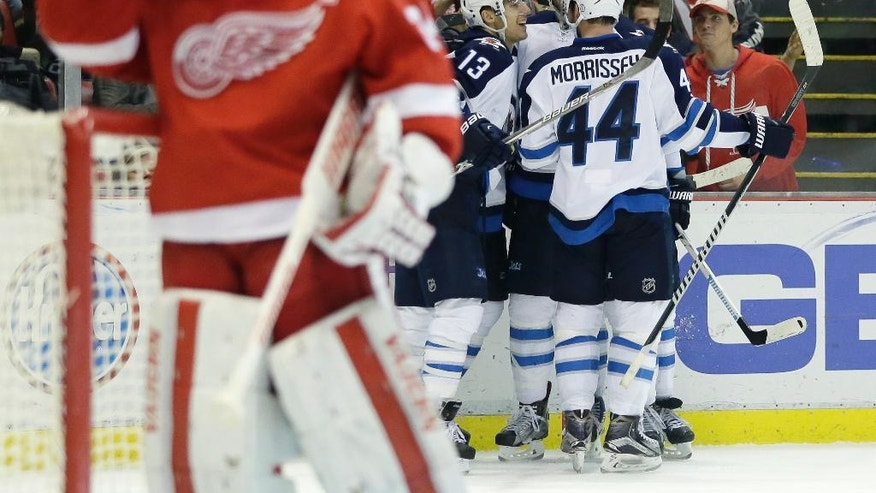 Winnipeg Jets left wing Brandon Tanev (13) celebrates with teammates after scoring against Detroit Red Wings goalie Petr Mrazek, left, of the Czech Republic, during the third period of an NHL hockey game Friday, Nov. 4, 2016, in Detroit. The Jets defeated the Red Wings 5-3. (AP Photo/Duane Burleson)