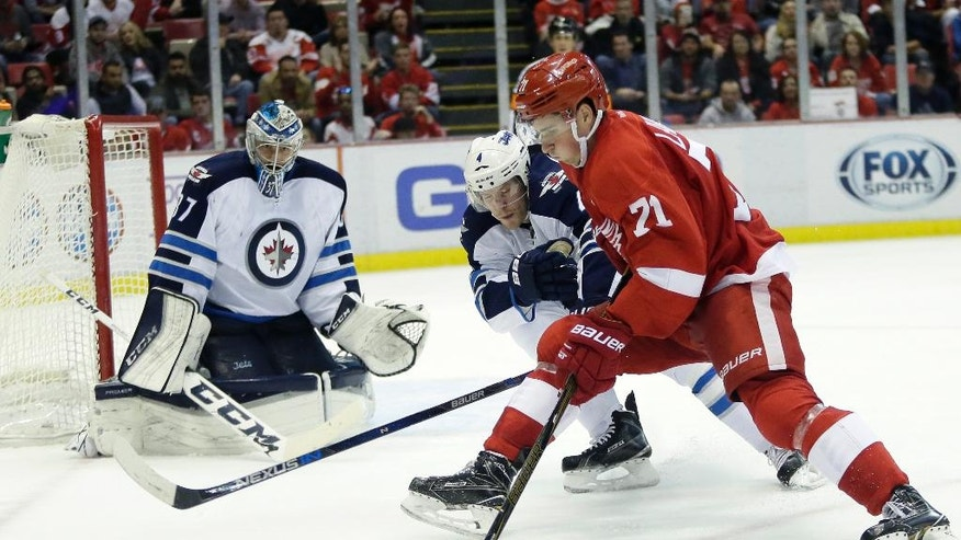 Detroit Red Wings center Dylan Larkin (71) tries to get around Winnipeg Jets defenseman Paul Postma (4) to take a shot on Jets goalie Connor Hellebuyck, left, during the second period of an NHL hockey game Friday, Nov. 4, 2016, in Detroit. (AP Photo/Duane Burleson)