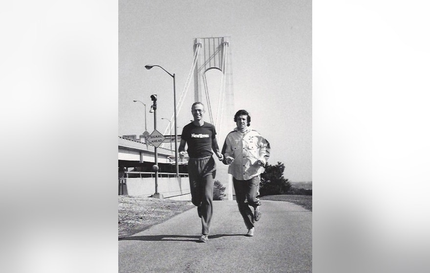 In this undated photo provided by New York City Marathon Co-founder George Hirsch, Hirsch, left, and marathoner Frank Shorter run parallel to the Belt Parkway with the Verrazano–Narrows Bridge in the background in New York. Shorter was secretly paid $3,000 for running in the first five-borough New York City Marathon in 1976. (George Hirsch via AP)