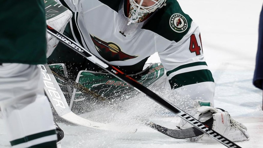Minnesota Wild goalie Devan Dubnyk makes a save against the Colorado Avalanche during the first period of an NHL hockey game, Saturday, Nov. 5, 2016, in Denver. (AP Photo/Jack Dempsey)