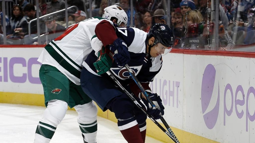 Minnesota Wild defenseman Ryan Suter (20) and Colorado Avalanche right wing Rene Bourque (17) fight for possession during the first period of an NHL hockey game, Saturday, Nov. 5, 2016, in Denver. (AP Photo/Jack Dempsey)