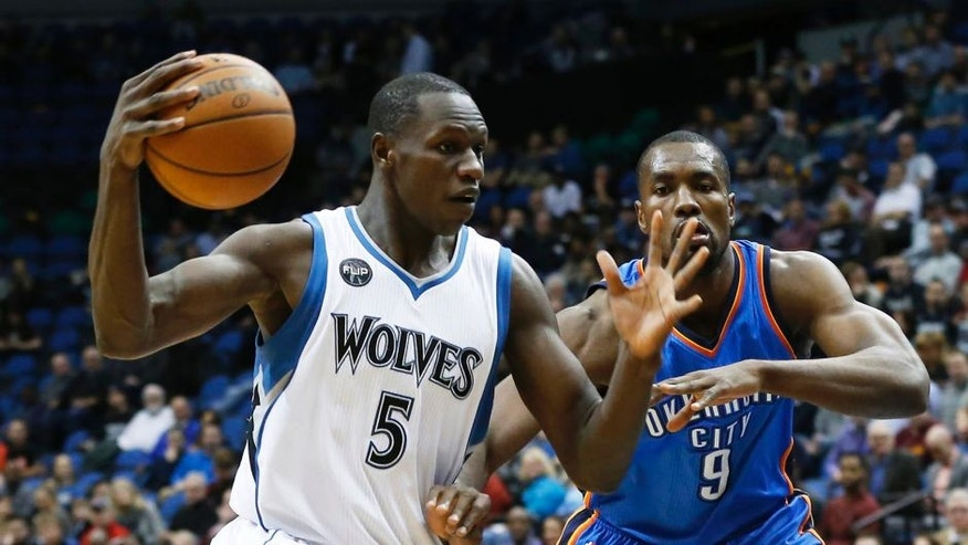 Minnesota Timberwolves' Gorgui Dieng, left, drives around Oklahoma City Thunder's Serge Ibaka in the first quarter of an NBA basketball game Tuesday, Jan. 12, 2016, in Minneapolis. (AP Photo/Jim Mone)