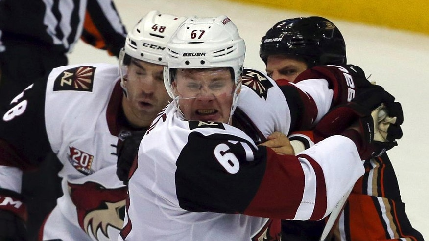 Arizona Coyotes' Jordan Martinook (48) and Lawson Crouse (67) fight with Anaheim Ducks' Kevin Bleksa (2) during the second period of an NHL hockey game in Anaheim, Calif., Friday, Nov. 4, 2016. (AP Photo/Reed Saxon)