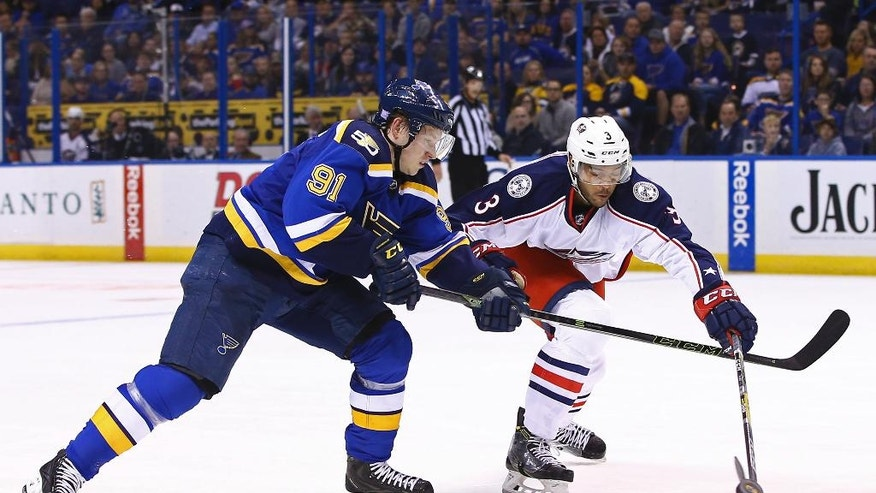 St. Louis Blues' Vladimir Tarasenko, left, of Russia, and Columbus Blue Jackets' Seth Jones reach for the puck during the second period of an NHL hockey game Saturday, Nov. 5, 2016, in St. Louis. (AP Photo/Billy Hurst)