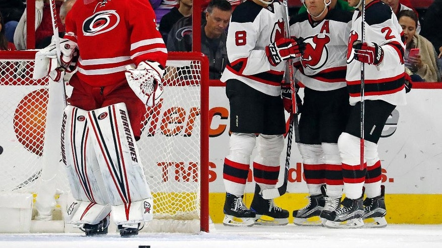 New Jersey Devils' Michael Cammalleri, center, celebrates his goal with teammates Beau Bennett (8) and John Moore (2) with Carolina Hurricanes goalie Eddie Lack (31) nearby during the second period of an NHL hockey game, Sunday, Nov. 6, 2016, in Raleigh, N.C. The Devils won 4-1. (AP Photo/Karl B DeBlaker)