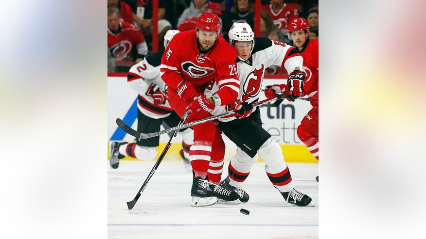 Carolina Hurricanes' Viktor Stalberg (25) gets tangled up with New Jersey Devils' Beau Bennett (8) during the first period of an NHL hockey game, Sunday, Nov. 6, 2016, in Raleigh, N.C. (AP Photo/Karl B DeBlaker)