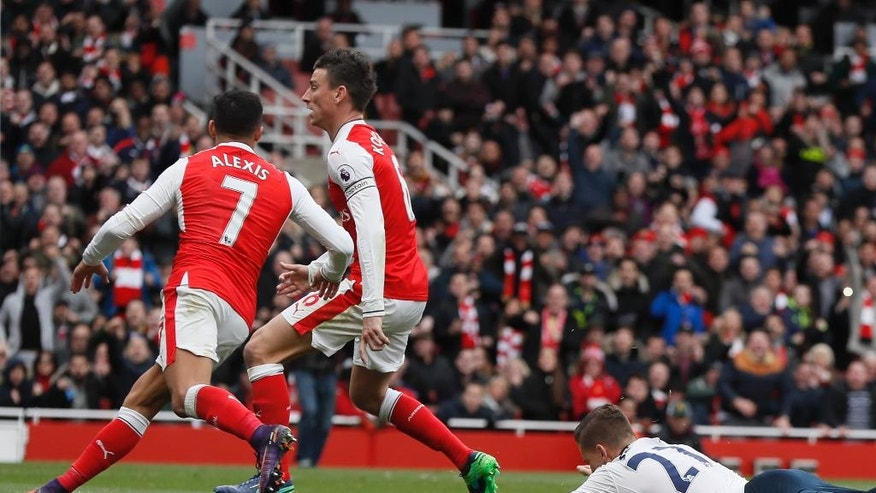 Tottenham's Kevin Wimmer lies on the ground after scoring an own goal as Arsenal's Alexis Sanchez, left, and Arsenal's Laurent Koscielny celebrate during the English Premier League soccer match between Arsenal and Tottenham Hotspur at Emirates stadium in London, Sunday, Nov. 6, 2016. (AP Photo/Kirsty Wigglesworth)