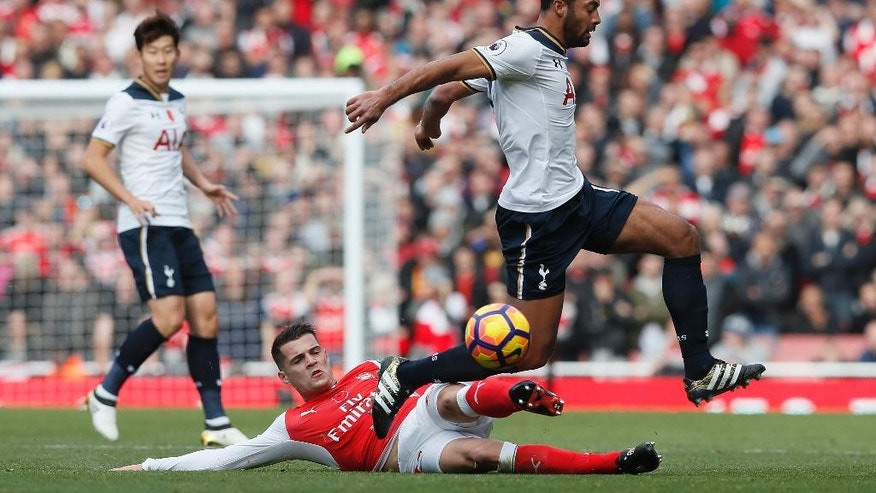 Arsenal's Granit Xhaka, on floor, vies for the ball with Tottenham's Mousa Dembele, right, during the English Premier League soccer match between Arsenal and Tottenham Hotspur at Emirates stadium in London, Sunday, Nov. 6, 2016. (AP Photo/Kirsty Wigglesworth)