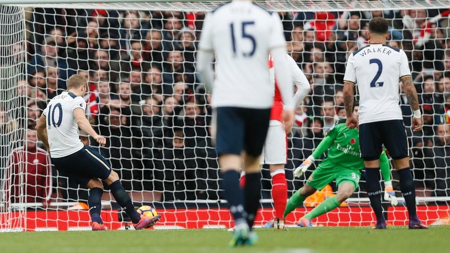 Tottenham's Harry Kane, left, scores a goal from a penalty during the English Premier League soccer match between Arsenal and Tottenham Hotspur at Emirates stadium in London, Sunday, Nov. 6, 2016. (AP Photo/Kirsty Wigglesworth)