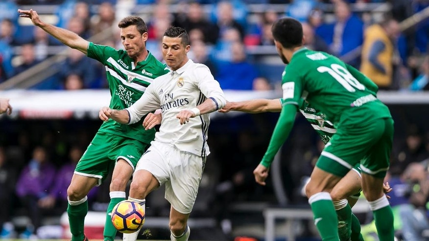 Real Madrid's Cristiano Ronaldo, center, duels for the ball with Leganes' Alberto Martin, left, during a Spanish La Liga soccer match between Real Madrid and Leganes at the Santiago Bernabeu stadium in Madrid, Spain, Sunday, Nov. 6, 2016. (AP Photo/Daniel Ochoa de Olza)