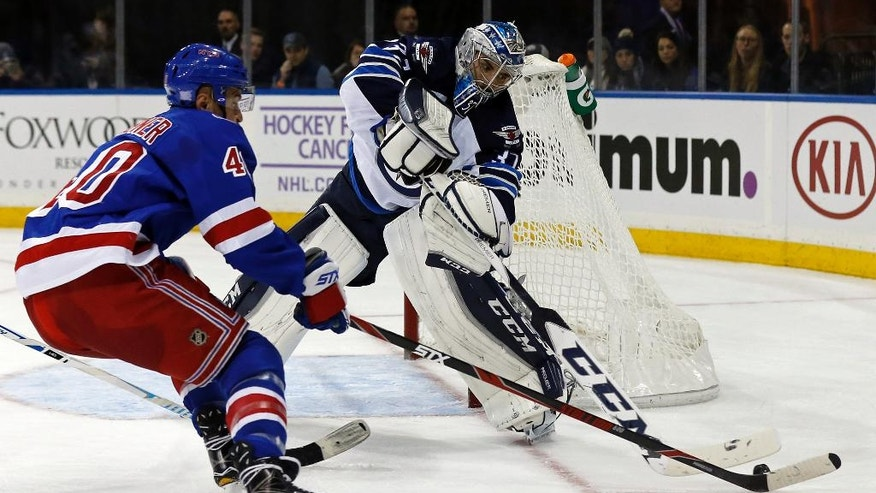 CORRECTS TO CONNOR HELLEBUYCK NOT MICHAEL HUTCHINSON Winnipeg Jets goalie Connor Hellebuyck knocks the puck away from New York Rangers right wing Michael Grabner (40) in the second period of an NHL hockey game, Sunday, Nov. 6, 2016, in New York. (AP Photo/Adam Hunger)
