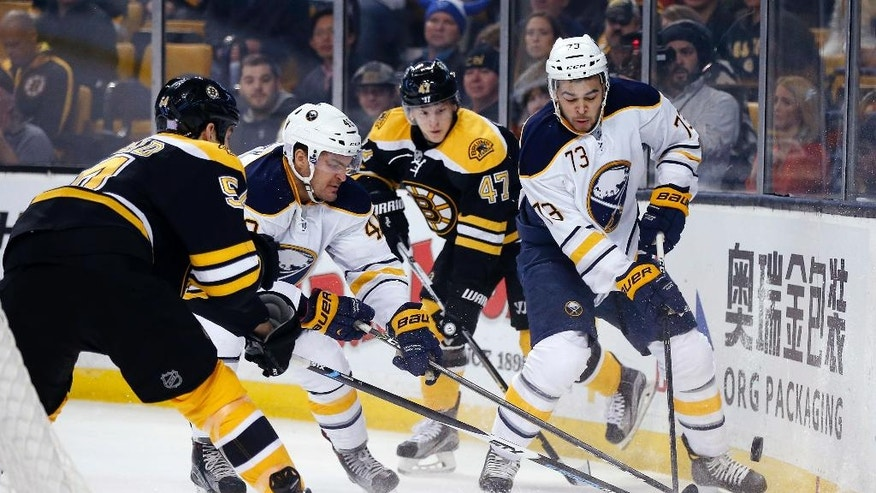 Boston Bruins' Adam McQuaid (54) and Torey Krug (47) battle Buffalo Sabres' William Carrier (48) and Nicholas Baptiste (73) during the first period of an NHL hockey game in Boston, Monday, Nov. 7, 2016. (AP Photo/Michael Dwyer)