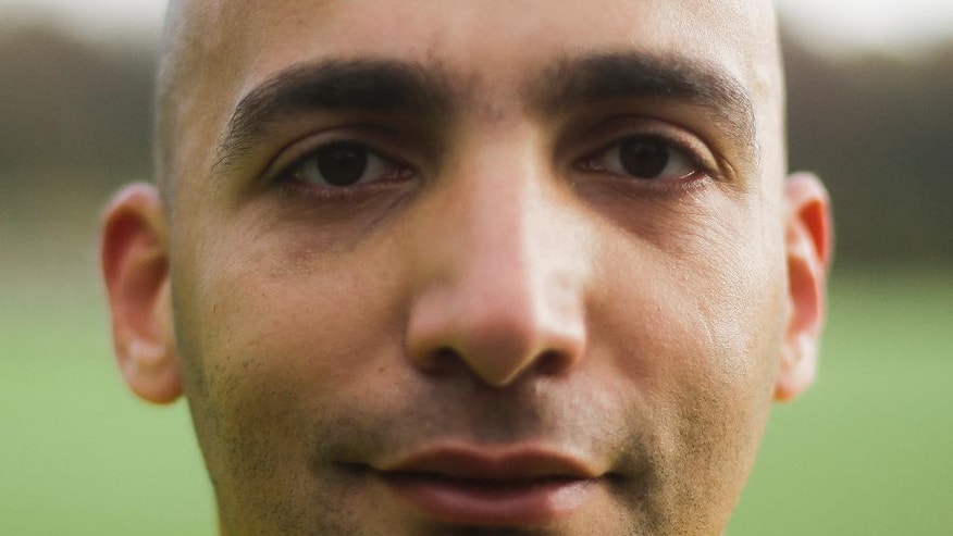 In this photo taken Sunday, Nov. 6, 2016, soccer referee Ammar Sahar, a 27-year-old refugee from Syria poses during the half time of a match of the amateur soccer league Berlin Liga in Berlin, Germany. Almost one year into his new life in Germany, Syrian refugee Sahar is well on his way to realizing his dream of becoming a Bundesliga referee. (AP Photo/Markus Schreiber).