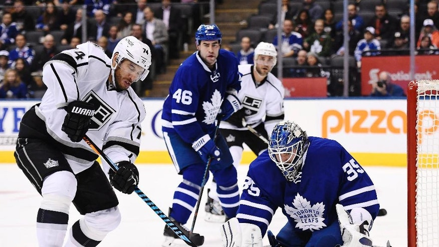 Toronto Maple Leafs goalie Jhonas Enroth (35) makes a save on Los Angeles Kings left wing Dwight King (74) as Maple Leafs defenseman Roman Polak (46) watches during the third period of an NHL hockey game Tuesday, Nov. 8, 2016, in Toronto. (Frank Gunn/The Canadian Press via AP)