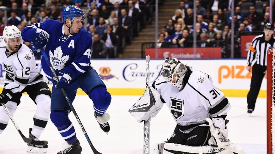 Los Angeles Kings goalie Peter Budaj (31) makes a save in front of Toronto Maple Leafs center Leo Komarov (47) as Kings' Alec Martinez (27) defends during the second period of an NHL hockey game Tuesday, Nov. 8, 2016, in Toronto. (Frank Gunn/The Canadian Press via AP)