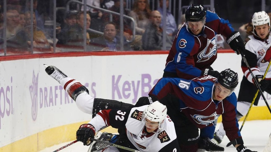 Arizona Coyotes center Tyler Gaudet, front, is pulled to the ice by Colorado Avalanche defenseman Nikita Zadorov, (16) of Russia, as defenseman Erik Johnson covers in the second period of an NHL hockey game Tuesday, Nov. 8, 2016, in Denver. (AP Photo/David Zalubowski)