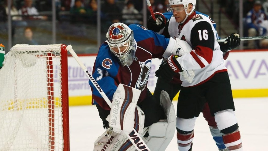 Colorado Avalanche goalie Calvin Pickard, left, fights off Arizona Coyotes left wing Max Domi while clearing the puck by the net in the second period of an NHL hockey game Tuesday, Nov. 8, 2016, in Denver. (AP Photo/David Zalubowski)