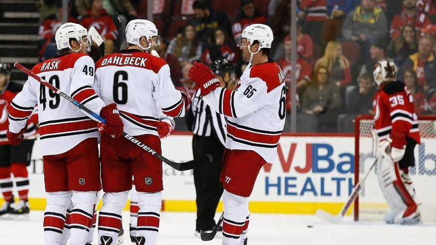 Carolina Hurricanes defenseman Klas Dahlbeck (6) celebrates with teammates after scoring a goal on New Jersey Devils goalie Cory Schneider, right rear, during the second period of an NHL hockey game, Tuesday, Nov. 8, 2016, in Newark, N.J. (AP Photo/Adam Hunger)
