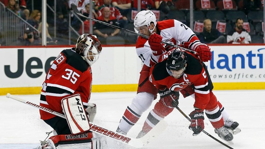 New Jersey Devils goalie Cory Schneider (35) makes a save in front of Devils defenseman Andy Greene (6) and Carolina Hurricanes right wing Lee Stempniak (21) during the first period of an NHL hockey game, Tuesday, Nov. 8, 2016, in Newark, N.J. (AP Photo/Adam Hunger)