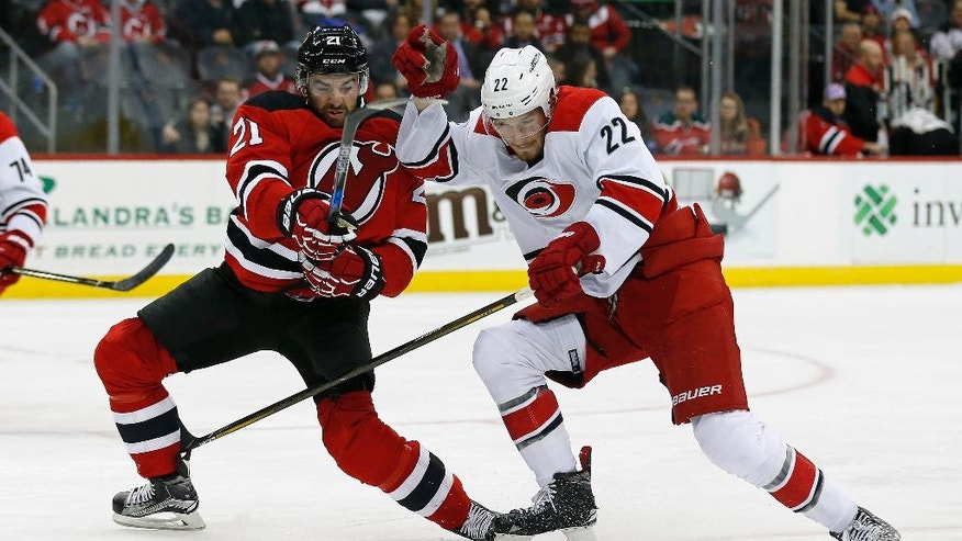 New Jersey Devils right wing Kyle Palmieri (21) battles for control of the puck with Carolina Hurricanes defenseman Brett Pesce (22) during the second period of an NHL hockey game, Tuesday, Nov. 8, 2016, in Newark, N.J. (AP Photo/Adam Hunger)