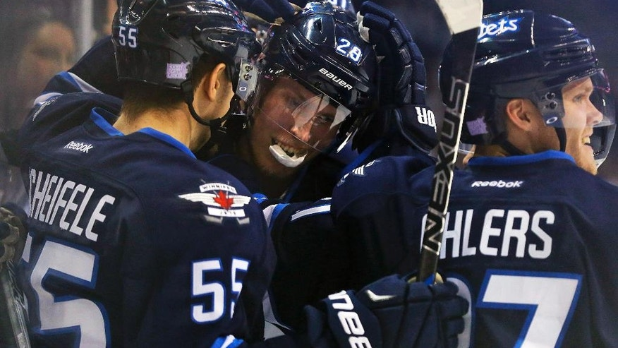 Winnipeg Jets' Patrik Laine (29) celebrates his third goal of the night with Mark Scheifele (55) and Nikolaj Ehlers (27) during the second period of an NHL hockey game against the Dallas Stars, Tuesday, Nov. 8, 2016, Winnipeg, Manitoba. (John Woods/The Canadian Press via AP)