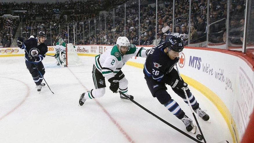 Dallas Stars' Dan Hamhuis (2) chases after Winnipeg Jets' Blake Wheeler (26) in the corner during the second period of an NHL hockey game Tuesday, Nov. 8, 2016, Winnipeg, Manitoba. (John Woods/The Canadian Press via AP)