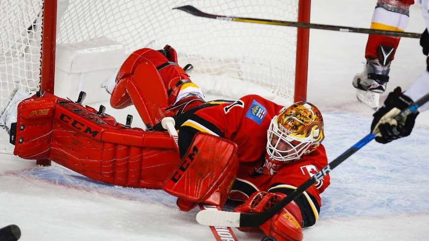 Calgary Flames goalie Brian Elliott dives for the puck during the second period of the team's NHL hockey game against the Dallas Stars on Thursday, Nov. 10, 2016, in Calgary, Alberta. (Jeff McIntosh/The Canadian Press via AP)
