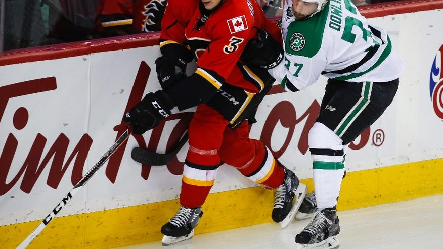 Dallas Stars' Justin Dowling, right, checks Calgary Flames' Jyrki Jokipakka, from Finland, during the second period of an NHL hockey game Thursday, Nov. 10, 2016, in Calgary, Alberta. (Jeff McIntosh/The Canadian Press via AP)
