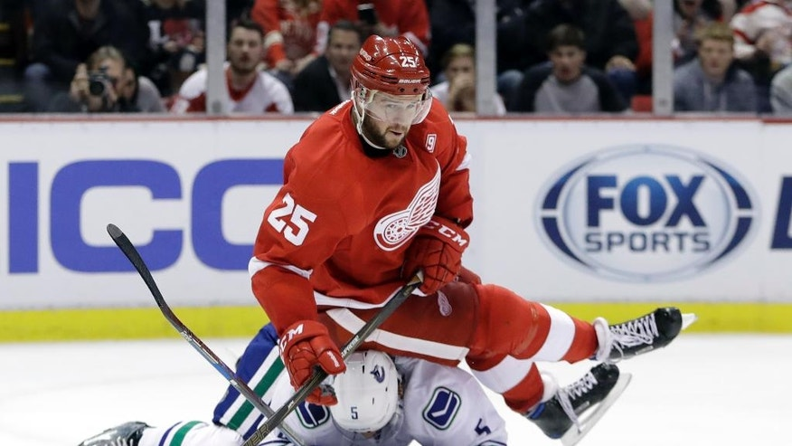 Detroit Red Wings defenseman Mike Green (25) falls over Vancouver Canucks defenseman Luca Sbisa (5) after passing the puck during the second period of an NHL hockey game, Thursday, Nov. 10, 2016, in Detroit. (AP Photo/Carlos Osorio)