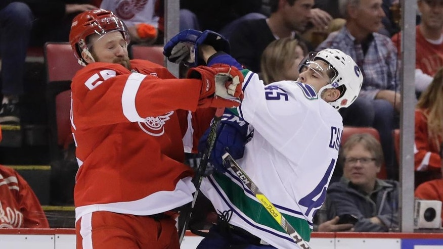 Detroit Red Wings defenseman Niklas Kronwall (55) checks Vancouver Canucks center Michael Chaput (45) during the first period of an NHL hockey game, Thursday, Nov. 10, 2016, in Detroit. (AP Photo/Carlos Osorio)