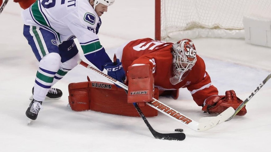 Vancouver Canucks right wing Derek Dorsett (15) tries shooting the puck past Detroit Red Wings goalie Jimmy Howard (35) during the third period of an NHL hockey game, Thursday, Nov. 10, 2016, in Detroit. (AP Photo/Carlos Osorio)