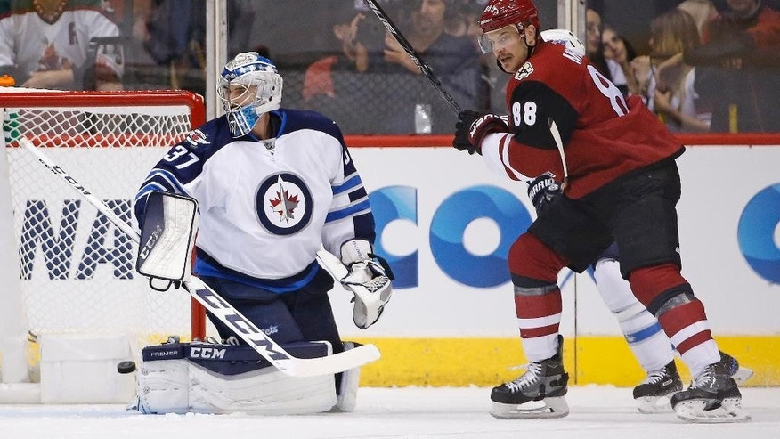 Winnipeg Jets goalie Connor Hellebuyck (37) looks for the puck after Arizona Coyotes' Radim Vrbata scores a goal as Coyotes' left wing Jamie McGinn (88) creates a screen during the first period of an NHL hockey game Thursday, Nov. 10, 2016, in Glendale, Ariz. (AP Photo/Ross D. Franklin)