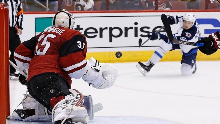 Arizona Coyotes goalie Louis Domingue (35) slides over the make a save against a shot by Winnipeg Jets center Alexander Burmistrov (91) during the first period of an NHL hockey game Thursday, Nov. 10, 2016, in Glendale, Ariz. (AP Photo/Ross D. Franklin)