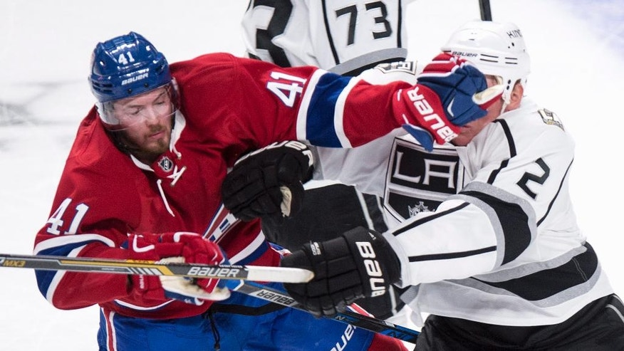 Los Angeles Kings' Matt Greene, right, gets a glove in the face from Montreal Canadiens' Paul Byron during the second period of an NHL hockey game Thursday, Nov. 10, 2016, in Montreal. (Paul Chiasson/The Canadian Press via iAP)