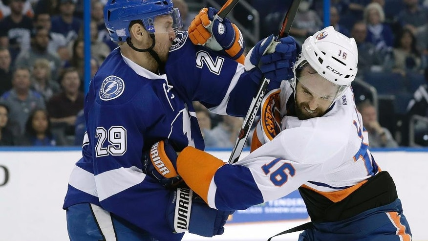 Tampa Bay Lightning defenseman Slater Koekkoek (29) and New York Islanders left wing Andrew Ladd (16) scrap during the first period of an NHL hockey game Thursday, Nov. 10, 2016, in Tampa, Fla. Ladd was penalized for high-sticking. (AP Photo/Chris O'Meara)