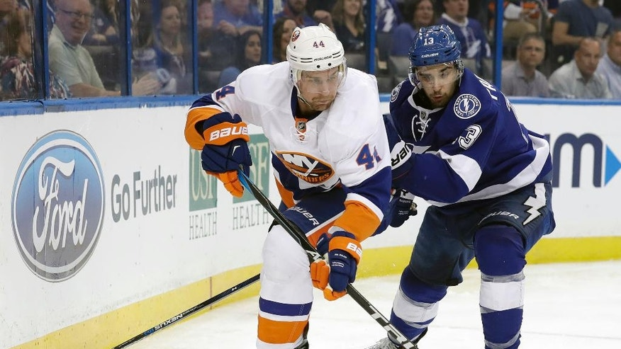 New York Islanders defenseman Calvin de Haan (44) moves the puck away from Tampa Bay Lightning center Cedric Paquette (13) during the second period of an NHL hockey game Thursday, Nov. 10, 2016, in Tampa, Fla. (AP Photo/Chris O'Meara)