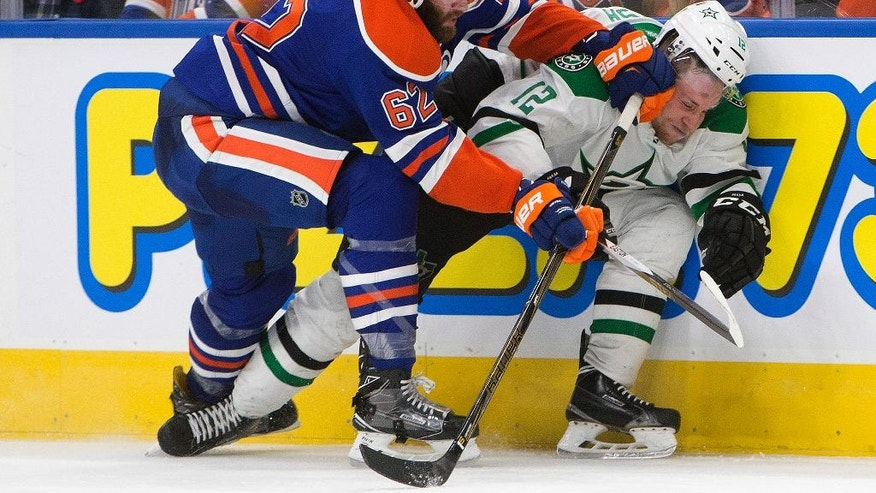 Dallas Stars' Radek Faksa (12) is checked by Edmonton Oilers' Eric Gryba (62) during the third period of an NHL hockey game Friday, Nov. 11, 2016, in Edmonton, Alberta. (Jason Franson/The Canadian Press via AP)