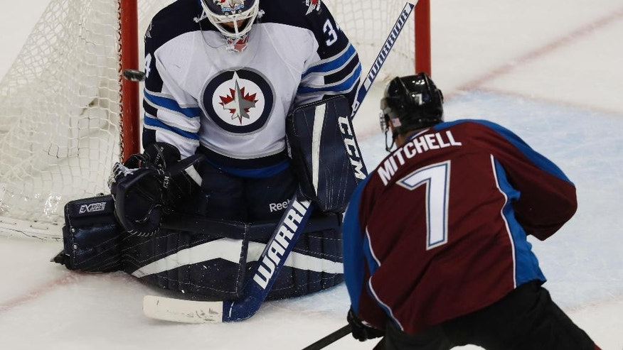 Winnipeg Jets goalie Michael Hutchinson, left, deflects a shot by Colorado Avalanche center John Mitchell during the third period of an NHL hockey game Friday, Nov. 11, 2016, in Denver. The Avalanche won 3-2 in overtime. (AP Photo/David Zalubowski)