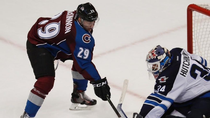 Winnipeg Jets goalie Michael Hutchinson, right, stops a shot off the stick of Colorado Avalanche center Nathan MacKinnon during overtime of an NHL hockey game Friday, Nov. 11, 2016, in Denver. The Avalanche won 3-2. (AP Photo/David Zalubowski)