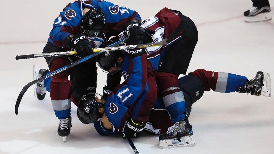 Colorado Avalanche defenseman Fedor Tyutin, top left, of Russia, joins left wing Gabriel Landeskog, top right, of Sweden, in congratulating right wing Rene Bourque after he scored the winning goal in overtime of an NHL hockey game against Winnipeg Jets late Friday, Nov. 11, 2016, in Denver. The Avalanche won 3-2 in overtime. (AP Photo/David Zalubowski)