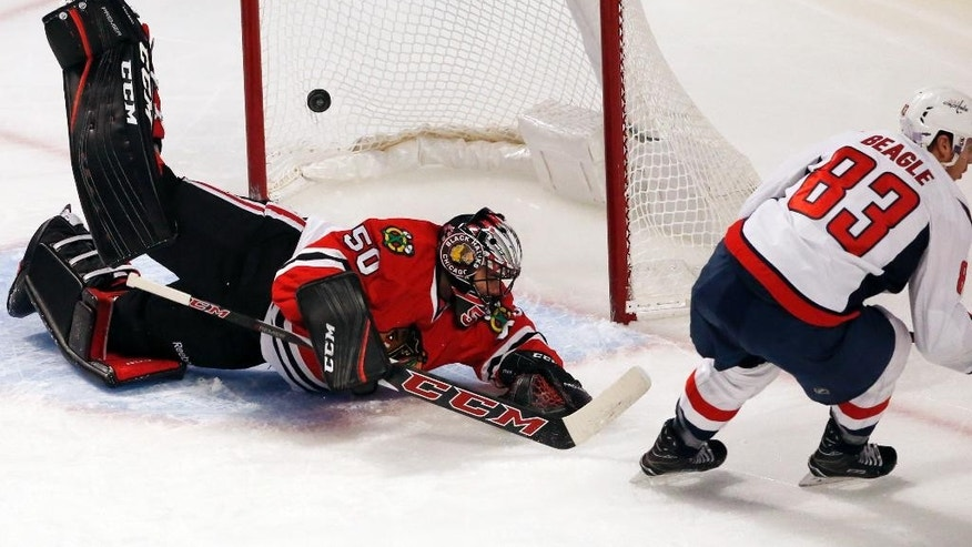 Chicago Blackhawks goalie Corey Crawford, left, is unable to make the play on a goal by Washington Capitals center Jay Beagle, right, during the first period of an NHL hockey game in Chicago, Friday, Nov. 11, 2016. (AP Photo/Nam Y. Huh)