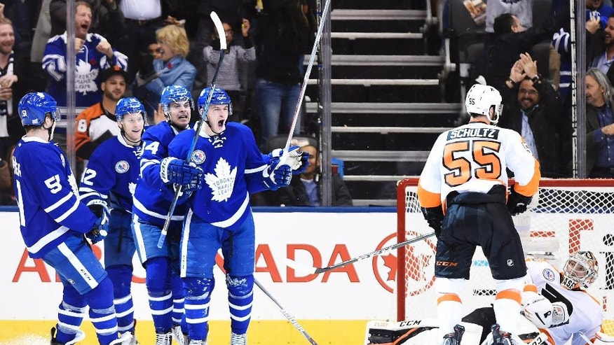 Toronto Maple Leafs center Zach Hyman (11) celebrates his goal on Philadelphia Flyers goalie Steve Mason (35) with teammates Jake Gardiner (51), Connor Brown (12) and Auston Matthews (34) as Philadelphia Flyers defenseman Nick Schultz (55) looks on during the third period of an NHL hockey game in Toronto, Friday, Nov. 11, 2016. (Nathan Denette/The Canadian Press via AP)
