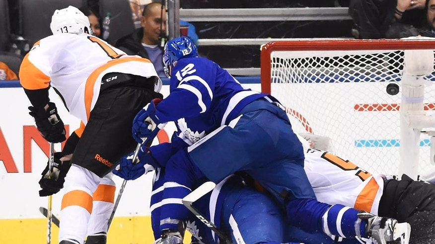 Toronto Maple Leafs center Zach Hyman (11) scores on Philadelphia Flyers goalie Steve Mason (35) as Philadelphia Flyers left wing Roman Lyubimov (13) and Toronto Maple Leafs right wing Connor Brown (12) battle during the third period of an NHL hockey game in Toronto, Friday, Nov. 11, 2016. (Nathan Denette/The Canadian Press via AP)