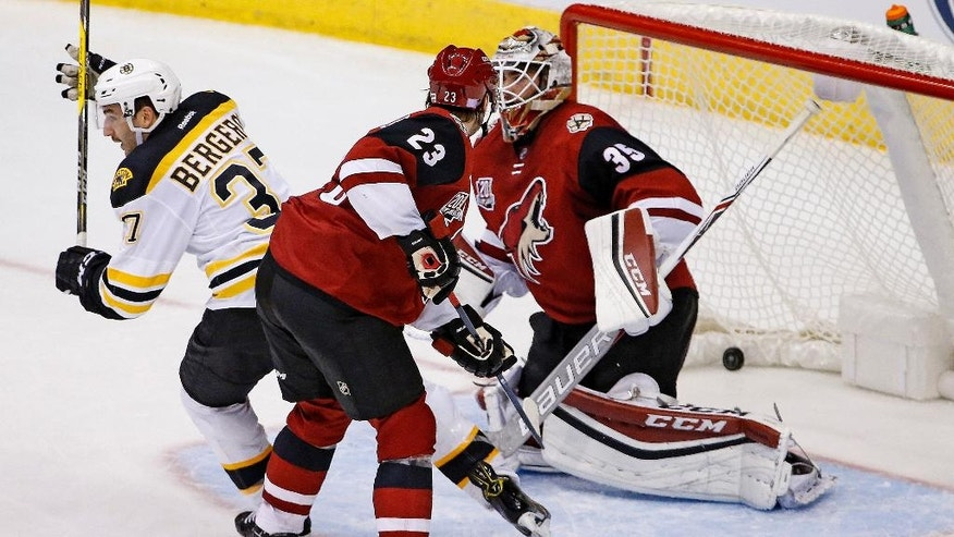 Boston Bruins center Patrice Bergeron (37) celebrates a goal by teammate David Pastrnak against Arizona Coyotes goalie Louis Domingue (35) as Coyotes defenseman Oliver Ekman-Larsson (23) looks for the puck during the second period of an NHL hockey game Saturday, Nov. 12, 2016, in Glendale, Ariz. (AP Photo/Ross D. Franklin)