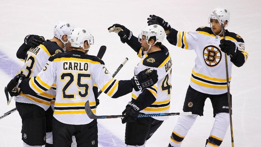 Boston Bruins defenseman Zdeno Chara, left, defenseman Brandon Carlo (25), right wing David Backes, second from right, and center Ryan Spooner (51) celebrate Spooner's goal against the Arizona Coyotes during the second period of an NHL hockey game Saturday, Nov. 12, 2016, in Glendale, Ariz. (AP Photo/Ross D. Franklin)