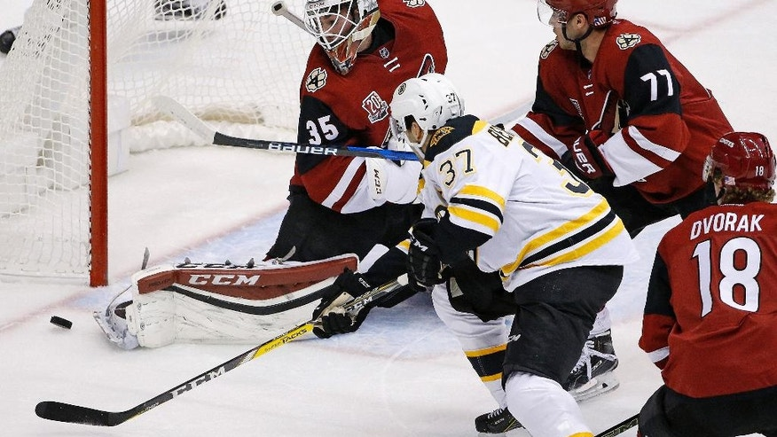 Arizona Coyotes goalie Louis Domingue (35) makes a save on a shot from Boston Bruins center Patrice Bergeron (37) as Coyotes defenseman Anthony DeAngelo (77) and center Christian Dvorak (18) help defend during the first period of an NHL hockey game Saturday, Nov. 12, 2016, in Glendale, Ariz. (AP Photo/Ross D. Franklin)