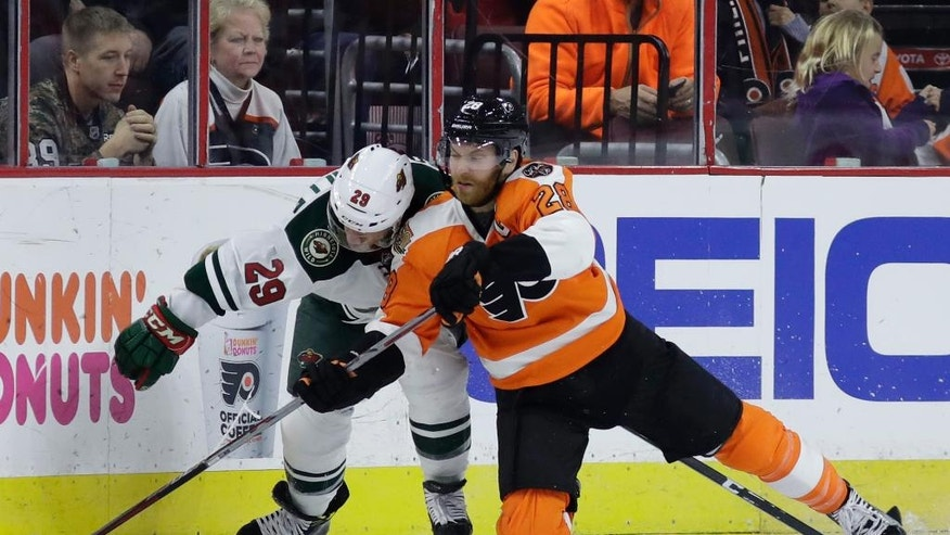 Philadelphia Flyers' Claude Giroux, right, and Minnesota Wild's Jason Pominville compete for the puck during the second period of an NHL hockey game, Saturday, Nov. 12, 2016, in Philadelphia. (AP Photo/Matt Slocum)