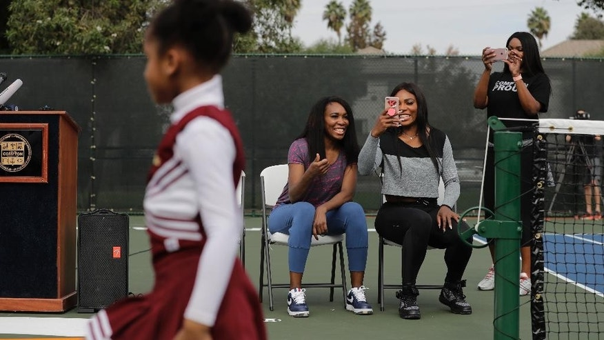 CORRECTS PARK SPELLING TO LUEDERS, NOT LEUDERS - Venus Williams, second from left, and sister Serena watch a performance by the Compton Sounders drill team during a dedication ceremony of the Lueders Park tennis courts Saturday, Nov. 12, 2016, in Compton, Calif. The courts were dedicated in their name. (AP Photo/Jae C. Hong)