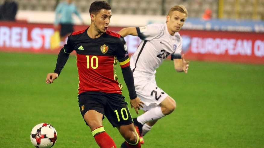 Belgium's Eden Hazard , foreground, scores against Estonia, during the World Cup Group H qualifying soccer match between Belgium and Estonia,  at the King Baudouin Stadium in Brussels on Sunday, Nov. 13, 2016.  (AP Photo/Olivier Matthys)